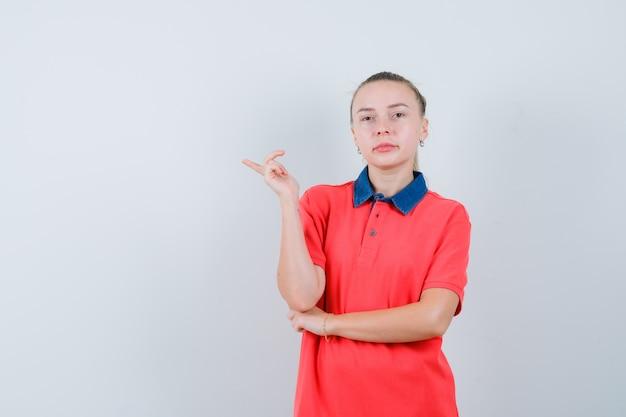 Młoda kobieta, wskazując na bok w koszulce i patrząc pewnie