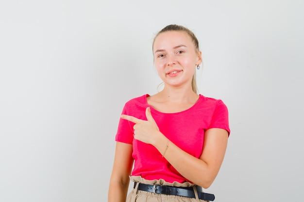 Młoda kobieta, wskazując na bok w koszulkach i spodniach i patrząc wesoło