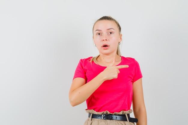 Młoda kobieta, wskazując na bok w koszulkach i spodniach i wyglądająca na zaskoczoną