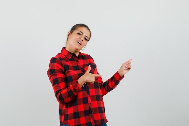 Młoda kobieta, wskazując na bok w kraciastej koszuli i patrząc pewnie, z przodu.