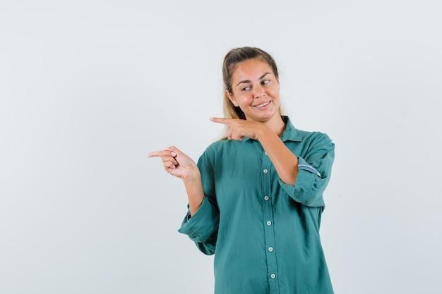 Młoda kobieta, wskazując na bok w niebieskiej koszuli i patrząc pewny
