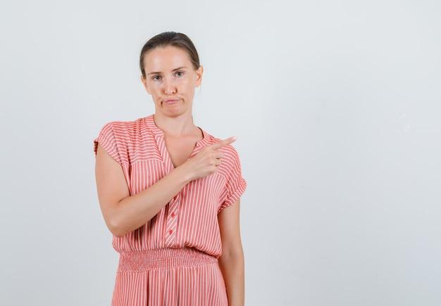 Młoda kobieta, wskazując na bok w pasiastej sukience i patrząc ponuro. przedni widok.
