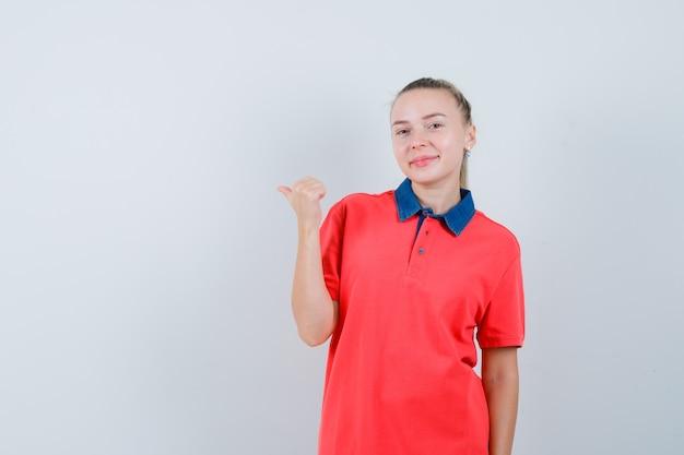 Młoda kobieta, wskazując na bok z kciukiem w koszulce i patrząc wesoło