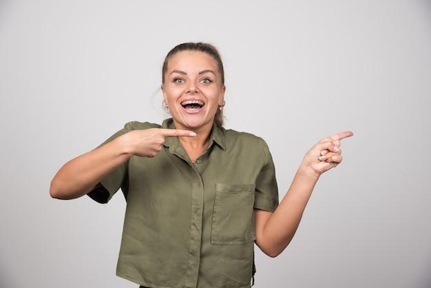 Młoda kobieta, wskazując na coś na szarej ścianie.