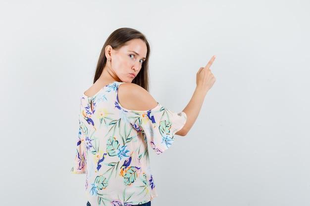 Młoda kobieta, wskazując na coś, patrząc z powrotem w koszuli, widok z tyłu.