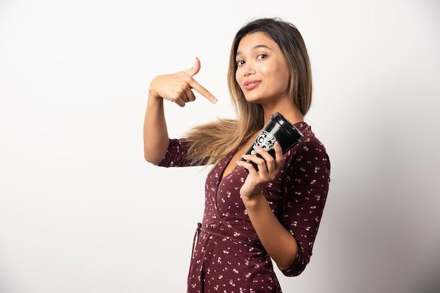 Młoda kobieta, wskazując na filiżankę napoju na białej ścianie.