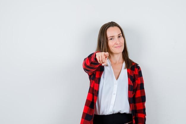 Młoda kobieta, wskazując na kamerę w ubranie i patrząc wesoły, widok z przodu.