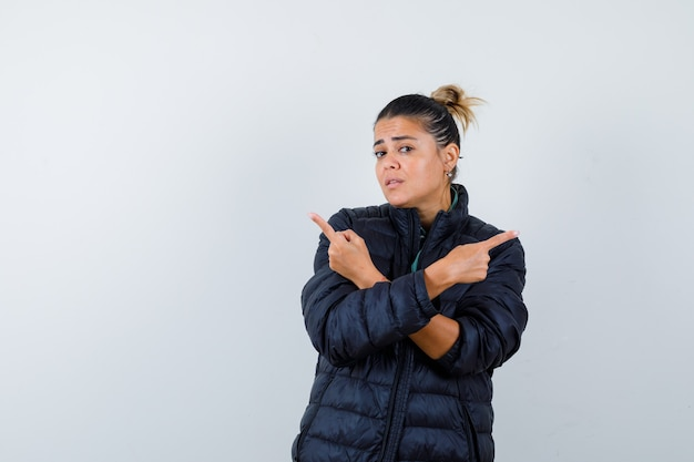 Młoda kobieta, wskazując na lewo i prawo w pikowanej kurtce i patrząc niezdecydowany. przedni widok.