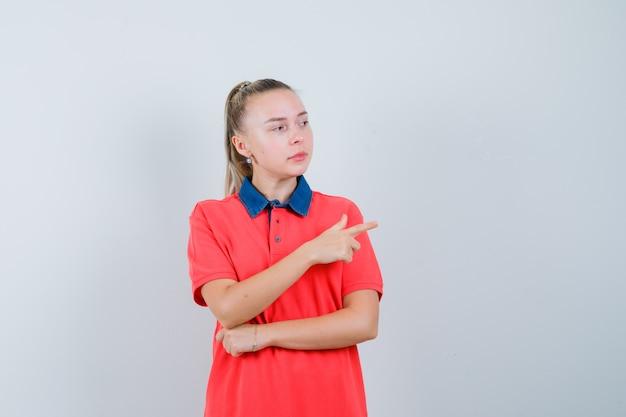 Młoda kobieta, wskazując na prawą stronę w t-shirt i wyglądająca pewnie