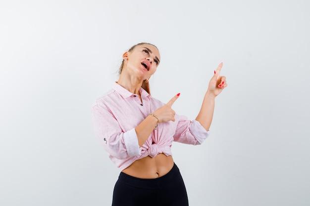 Młoda kobieta, wskazując na prawy górny róg w zwykłej koszuli, spodniach i wyglądającej na szczęśliwą. przedni widok.