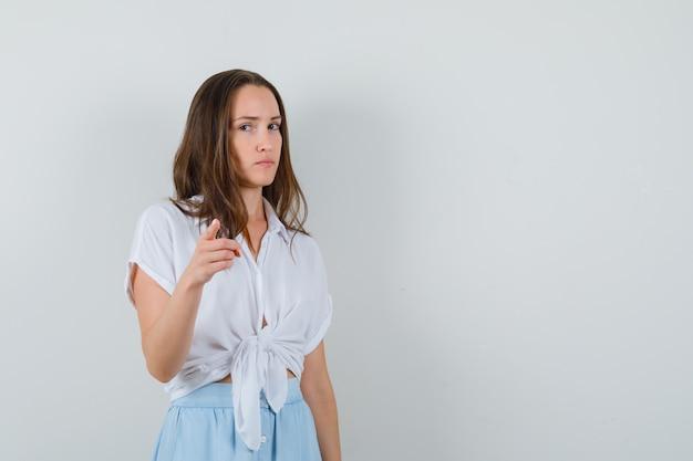 Młoda kobieta, wskazując na przód z palcem wskazującym w białej bluzce i jasnoniebieskiej spódnicy i patrząc poważnie