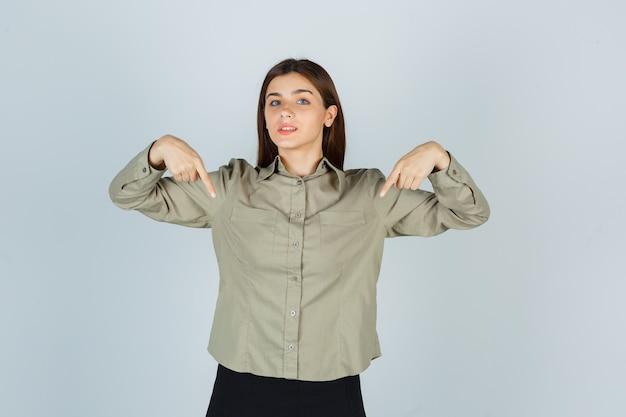 Młoda kobieta, wskazując na siebie w koszuli, spódnicy i patrząc dumny, widok z przodu.