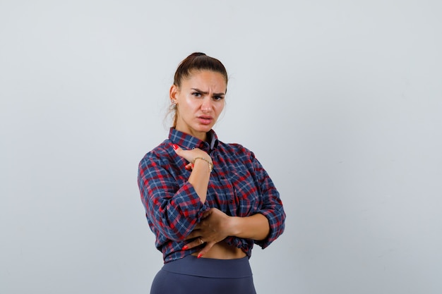 Młoda kobieta, wskazując na siebie w kraciastej koszuli, spodniach i patrząc niezdecydowany, widok z przodu.