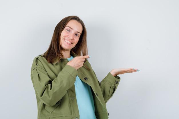 Młoda kobieta, wskazując na swoją dłoń rozłożoną na bok w koszulce, kurtce i wyglądającej wesoło. przedni widok.