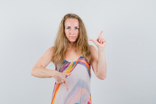Młoda kobieta wskazując palcami w górę iw dół w letniej sukience i wygląda rozsądnie