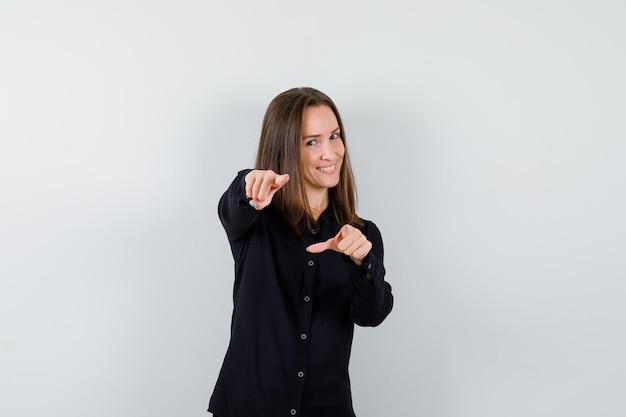 Młoda kobieta, wskazując palcami