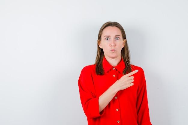 Młoda kobieta, wskazując palcem w czerwonej bluzce i patrząc w szoku, widok z przodu.