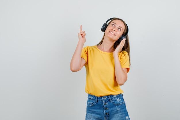 Młoda kobieta wskazując palcem w t-shirt, spodenki, słuchawki i szuka zadowolony. przedni widok.