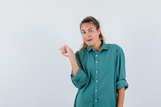 Młoda kobieta wskazując palcem wskazującym w zielonej bluzce i patrząc szczęśliwy