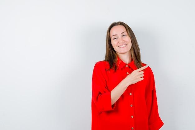 Młoda kobieta, wskazując prawo w czerwonej bluzce i patrząc wesoły, widok z przodu.
