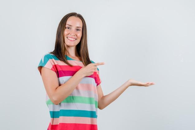 Młoda kobieta wskazując ręką rozłożoną na bok w t-shirt i patrząc wesoły, widok z przodu.