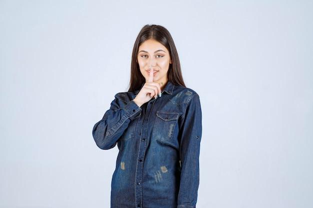 Młoda kobieta wskazując usta i prosząc o ciszę
