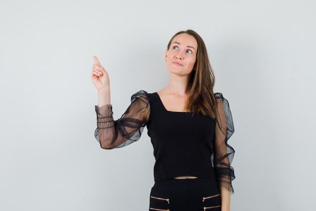 Młoda kobieta, wskazując w czarną bluzkę i patrząc skupiony. przedni widok.
