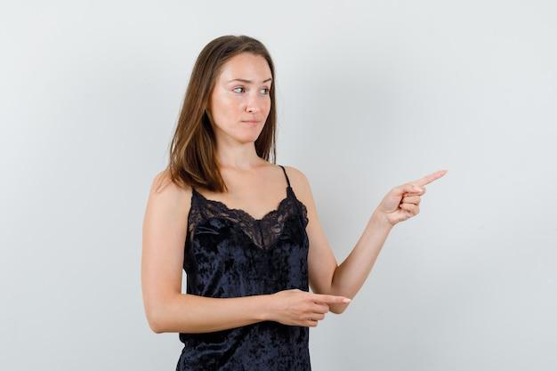 Młoda kobieta wskazując w czarny podkoszulek i patrząc niezdecydowanie