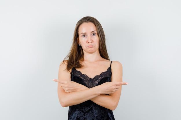 Młoda kobieta, wskazując w czarny podkoszulek i wyglądająca na zdezorientowaną.
