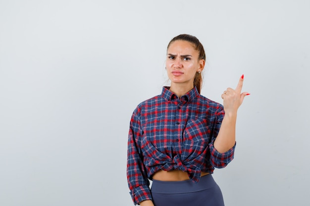 Młoda kobieta, wskazując w kraciaste koszule, spodnie i patrząc poważnie, widok z przodu.