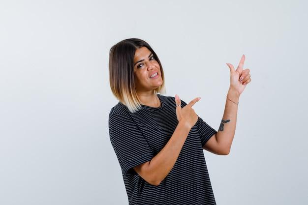 Młoda kobieta, wskazując w prawo z palcami wskazującymi w czarnej sukience i patrząc szczęśliwy. przedni widok.