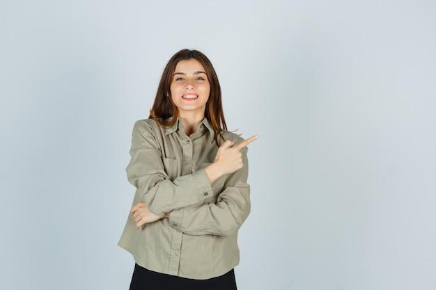 Młoda kobieta, wskazując w prawym górnym rogu koszuli, spódnicy i cieszę się