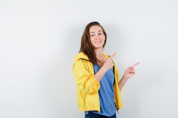Młoda kobieta, wskazując w prawym górnym rogu w t-shirt, kurtkę i patrząc wesoło, widok z przodu.