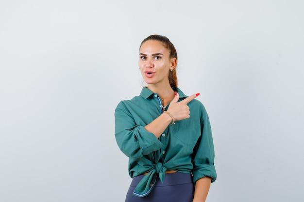 Młoda kobieta, wskazując w prawym górnym rogu w zielonej koszuli i patrząc zdziwiony. przedni widok.