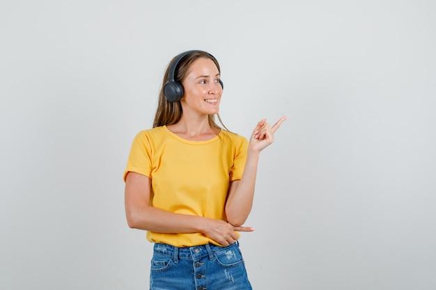 Młoda kobieta wskazując w t-shirt, spodenki, słuchawki i patrząc zadowolony. przedni widok.