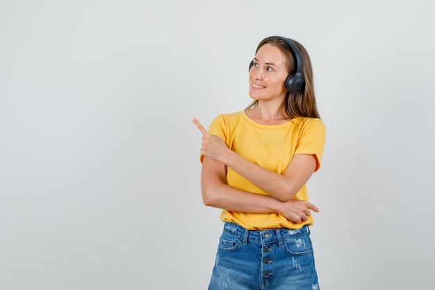 Młoda kobieta wskazując w t-shirt, spodenki, słuchawki i szuka zadowolony