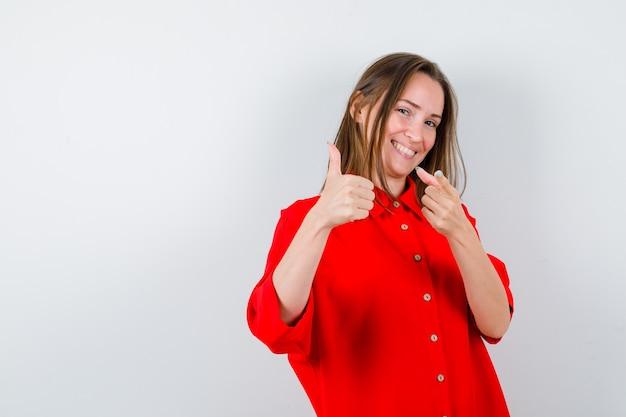 Młoda kobieta, wskazując z przodu, pokazując kciuk w czerwonej bluzce i wyglądający atrakcyjnie, widok z przodu.
