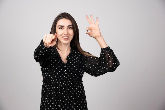 Młoda kobieta wskazująca aparat na szarej ścianie. zdjęcie wysokiej jakości