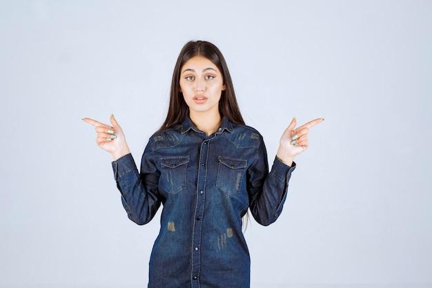 Młoda kobieta, wskazująca na coś lub prezentująca coś po obu stronach