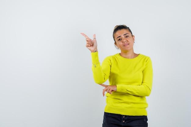 Młoda kobieta wskazująca palcem wskazującym w lewo w żółtym swetrze i czarnych spodniach i wygląda na szczęśliwą
