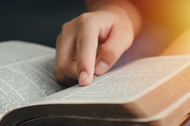 Młoda kobieta wskazująca prawdziwe wersety pisma świętego. czytając biblię rano przy parapecie