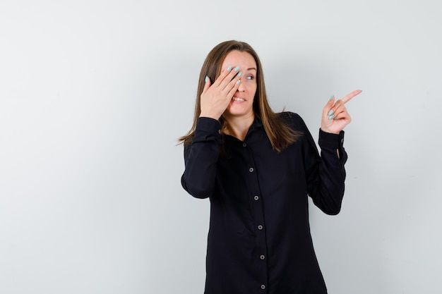 Młoda kobieta wskazująca w prawo i zakrywająca oko