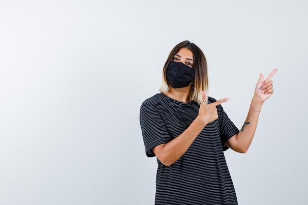 Młoda kobieta wskazująca w prawo z palcami wskazującymi w czarnej sukience, czarnej masce i poważny widok z przodu.