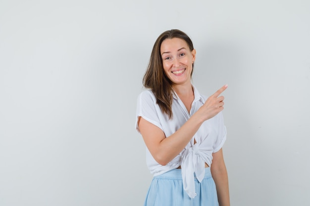 Młoda kobieta wskazująca w prawo z palcem wskazującym w białej bluzce i jasnoniebieskiej spódnicy i wyglądająca wesoło