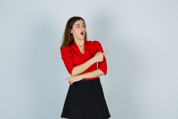 Młoda kobieta wskazująca w prawo z palcem wskazującym w czerwonej bluzce, czarnej spódnicy i patrząc zaskoczony