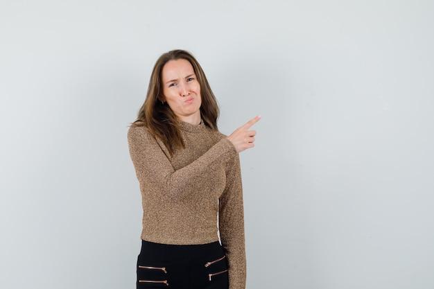 Młoda kobieta wskazująca w prawo z palcem wskazującym w pozłacanym swetrze i czarnych spodniach i wygląda zamyślona