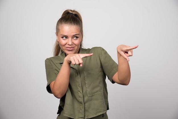 Młoda kobieta wskazuje coś w zielonym stroju.