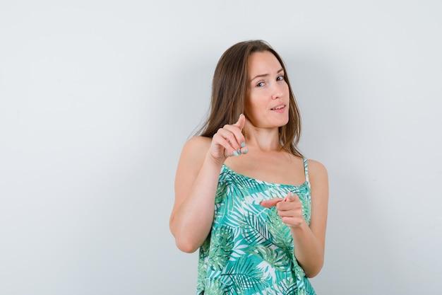 Młoda kobieta wskazuje do przodu i wygląda rozsądnie, przedni widok.