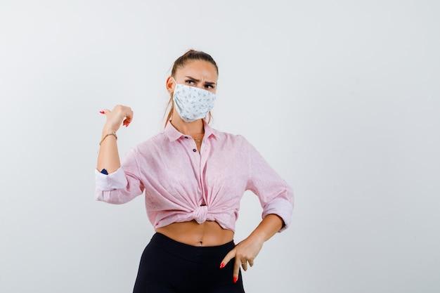 Młoda kobieta wskazuje kciuk w lewo, trzymając rękę na biodrze w koszuli, spodniach, masce medycznej i zamyślonym widoku z przodu.
