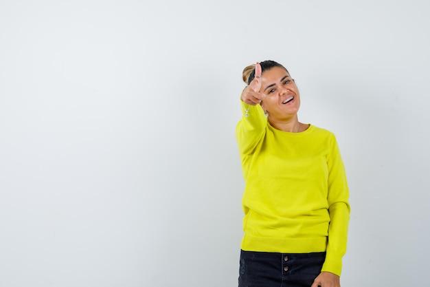 Młoda kobieta wskazuje na aparat palcem wskazującym w żółtym swetrze i czarnych spodniach i wygląda na szczęśliwą